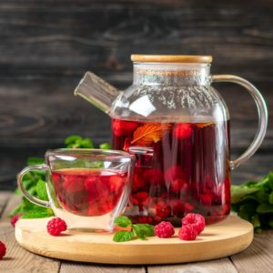 Herbal tea with berries, raspberries, mint leaves and hibiscus flowers in glass teapot and cup on wooden table Medicine for cold Vitamin drink Rustic style.
